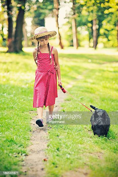 Little girl is walking her dog