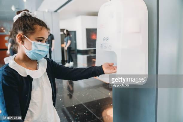 映画館のロビーの入り口で、小さな女の子が手指消毒剤で手を洗っている - 消毒用アルコール ストックフォトと画像