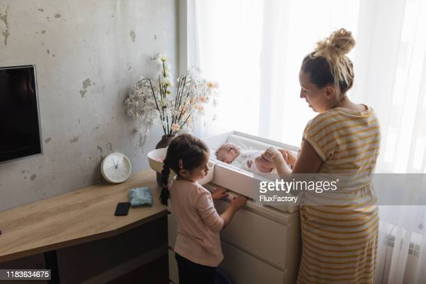 little girl jealous of her little baby girl - little girl taking off clothes stock photos and pictures