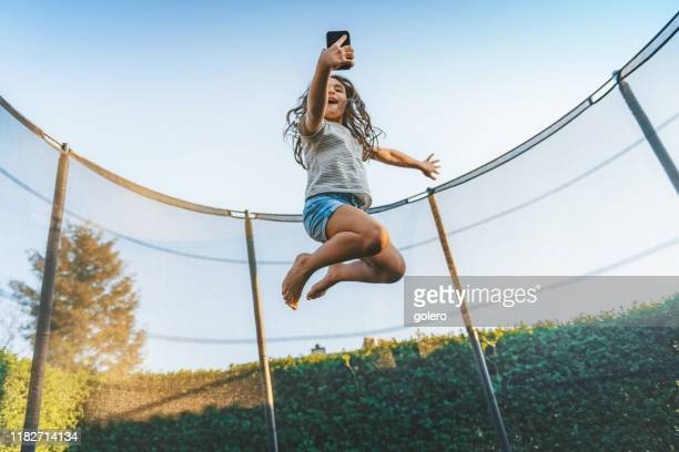 little girl jumping high on trampoline with mobile - wide stock pictures, royalty-free photos & images