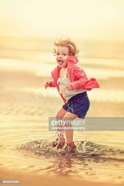 Little girl jumping in a puddle at the beach