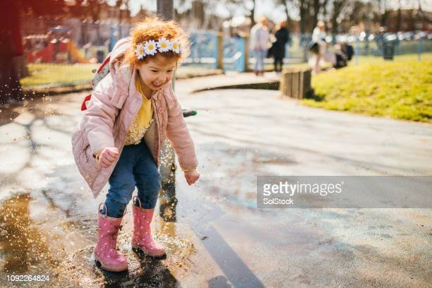 little girl jumping in a puddle of water - puddle stock pictures, royalty-free photos & images