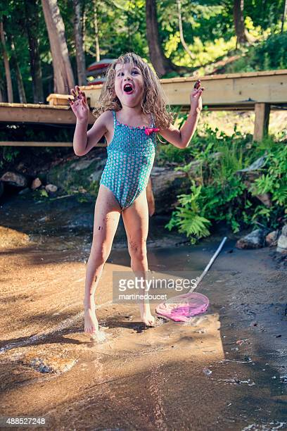Little girl jumping in lake water in summer nature.