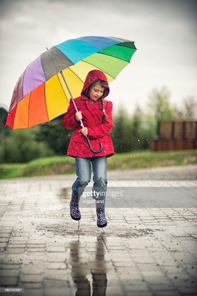 Little girl jumping in the rain : Stock Photo