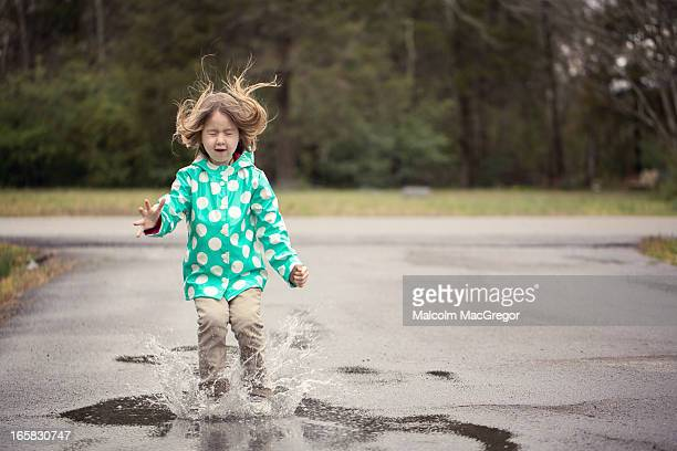 Little Girl Jumping into a Puddle
