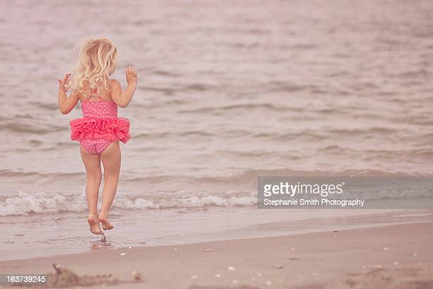 Little girl jumping near the ocean