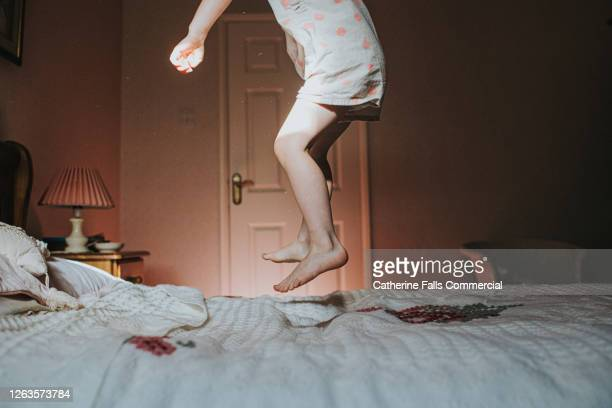 Little girl jumping on an Old fashioned Bed