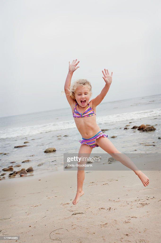 Little girl jumping on beach : Foto de stock