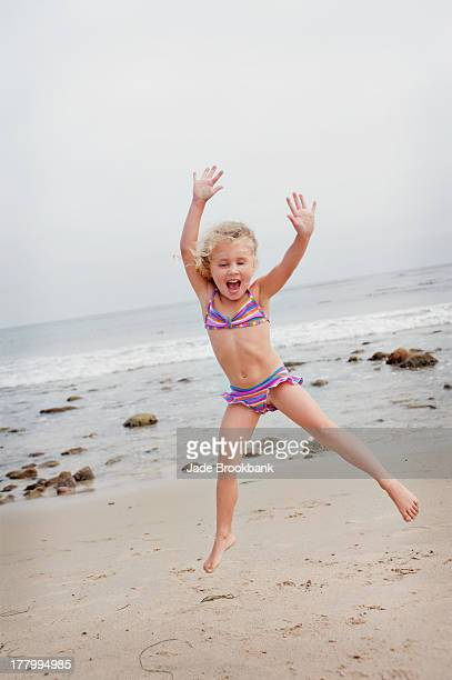 little girl jumping on beach - girl with legs spread stock photos and pictures