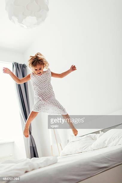 little girl jumping on the bed. - nachthemd stockfoto's en -beelden
