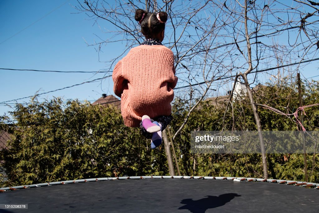 Little girl jumping on trampoline outdoors in springtime. : Stock Photo