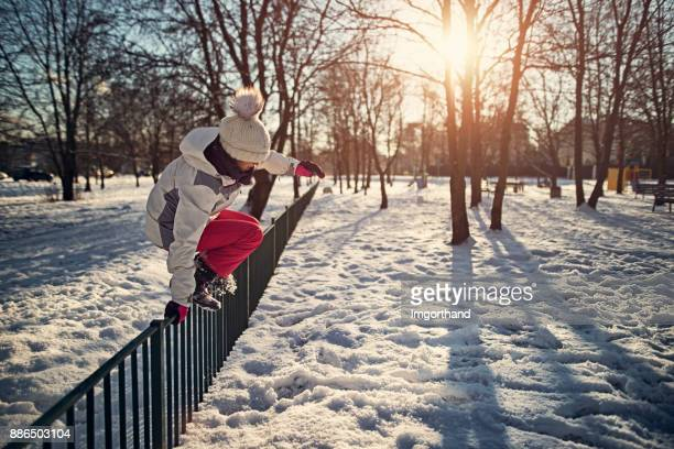 Little girl jumping over fence in winter city park