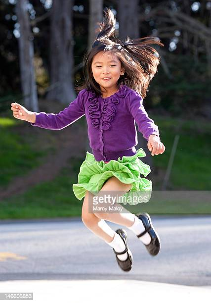 Little girl jumping up into the air.