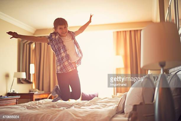 Little girl jumping with joy on parents bed.