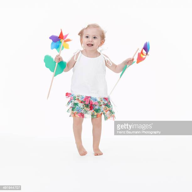 Little girl jumping with pinwheels