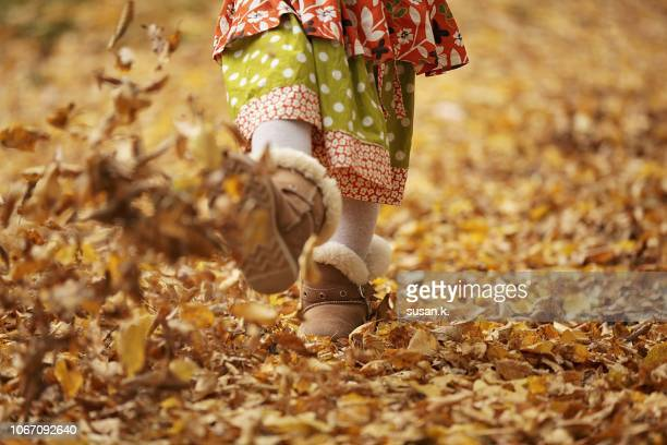 little girl kicking autumn leaves - kicking stock pictures, royalty-free photos & images