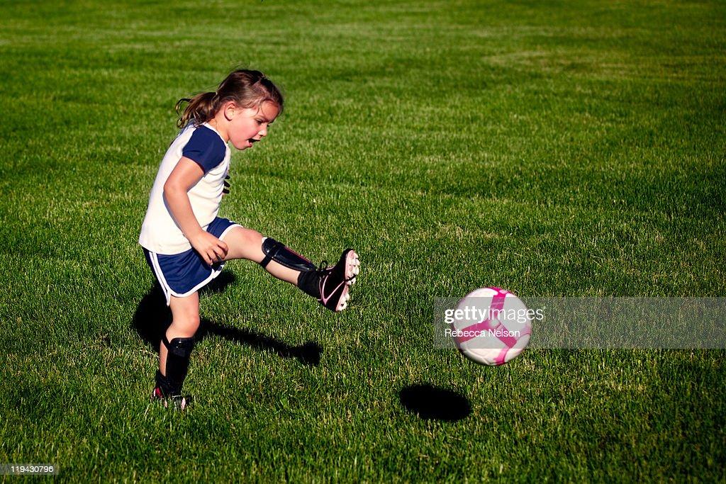 Little Girl Kicking Soccer Ball High-Res Stock Photo