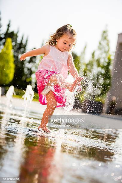 Little girl kicking water jet of fountain