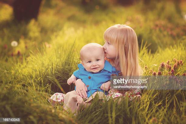little girl kissing a happy baby