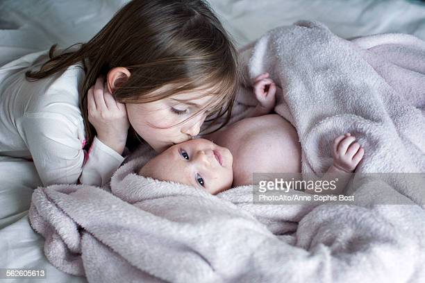 Little girl kissing baby brothers cheek on bed