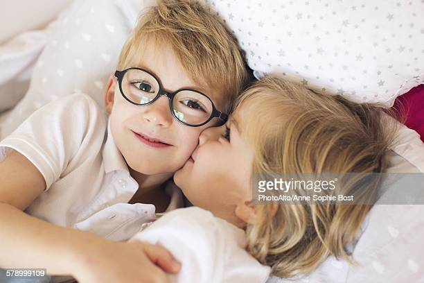 Little girl kissing big brother