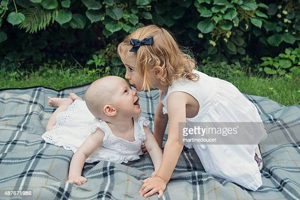 "little girl kissing happy baby sister on forehead outdoors summer. - ""martine doucet"" or martinedoucet stockfoto's en -beelden"