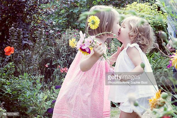 little girl kissing her baby sister outdoors - alleen meisjes stockfoto's en -beelden