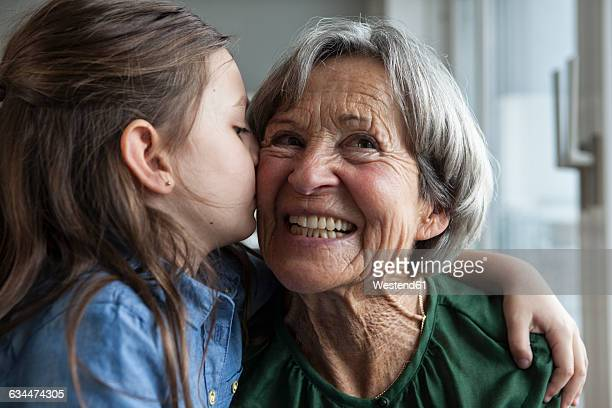 little girl kissing her grandmother - grandmother stock pictures, royalty-free photos & images