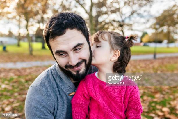 Little girl kissing her happy father in autumnal park