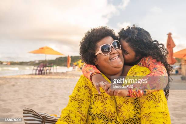 little girl kissing her mother and enjoying the beach - heavy stock pictures, royalty-free photos & images