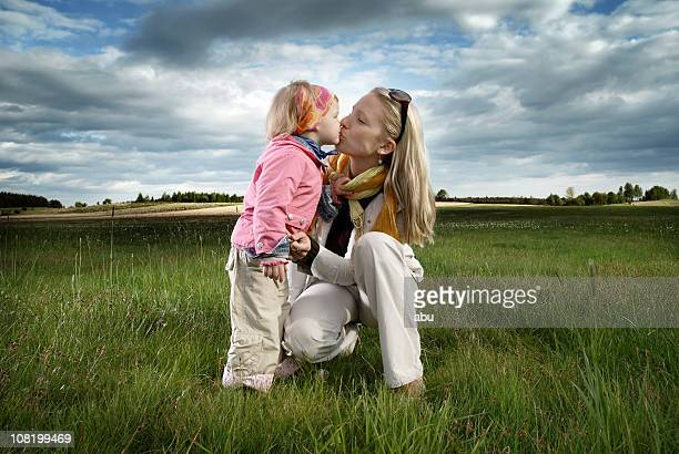 little girl kissing her mother in overcast field - kissing on the mouth stock photos and pictures
