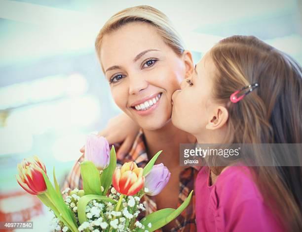 Rapariga beijar a sua mãe.