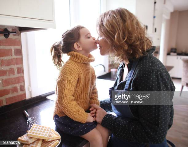 a little girl kissing her mum in the kitchen - affectueux photos et images de collection