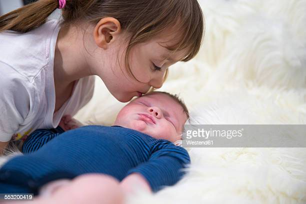Little girl kissing newborn brother