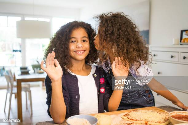 Little girl kissing sister in kitchen, baking pizza