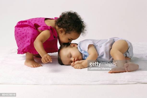 Little Girl Kissing Sleeping Infant
