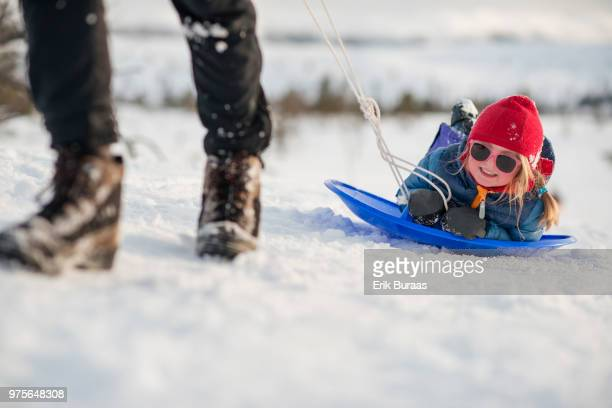 Little girl laughing and being pulled on a toboggan