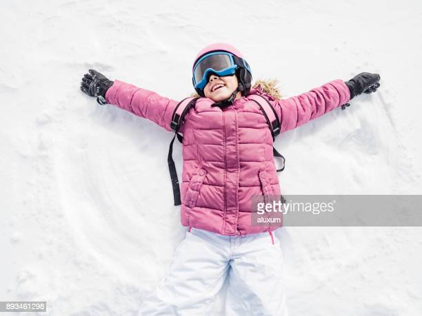 Little girl laughing and playing snow angel