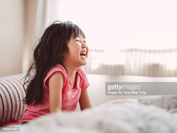 Little girl laughing joyfully in bed
