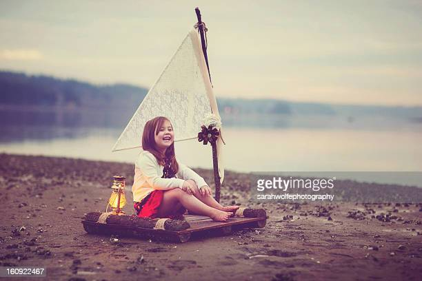 Little girl laughing on a raft by the ocean
