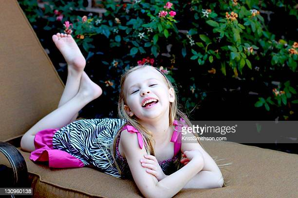 little girl laughing - barefoot feet up lying down girl stock photos and pictures