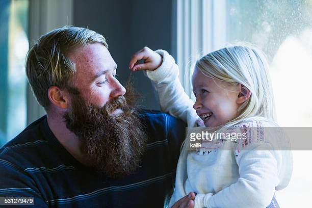 Little girl laughing, pulling daddy's whiskers