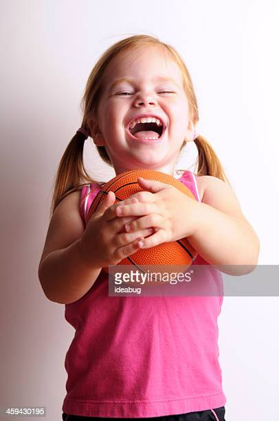 Little Girl Laughing While Holding a Basketball