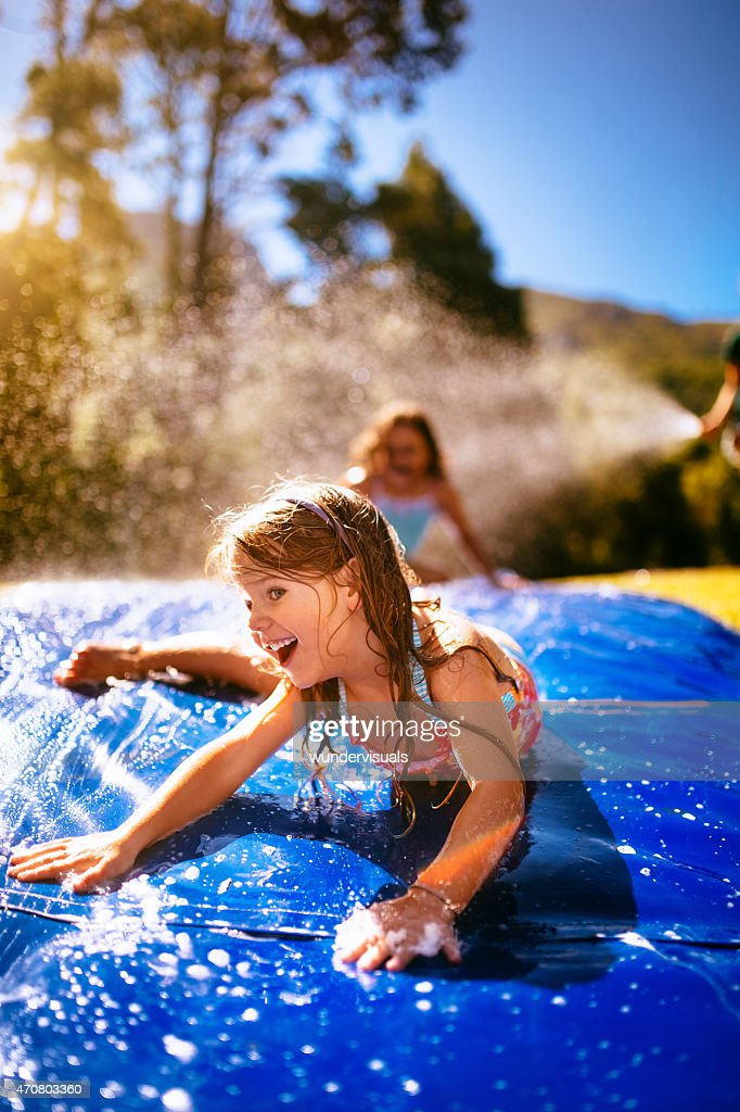 Little girl laughing while sliding down a water slide : Stock Photo