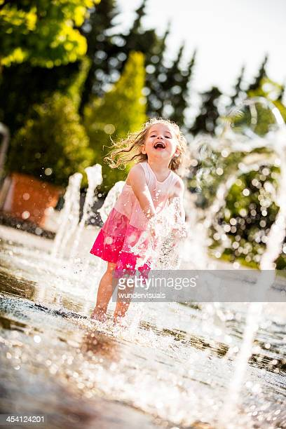 Little girl laughing while splashing water in fountain