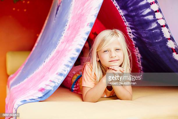 A little girl laying in a fort outside.