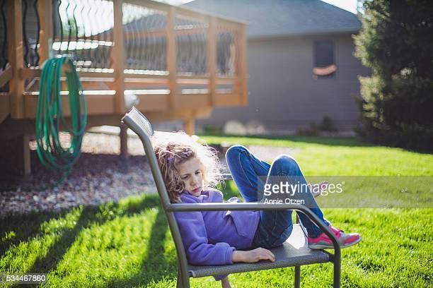 little girl laying in lawn chair - penalty fotografías e imágenes de stock