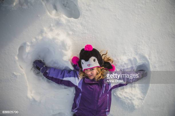 Little girl Laying in Snow