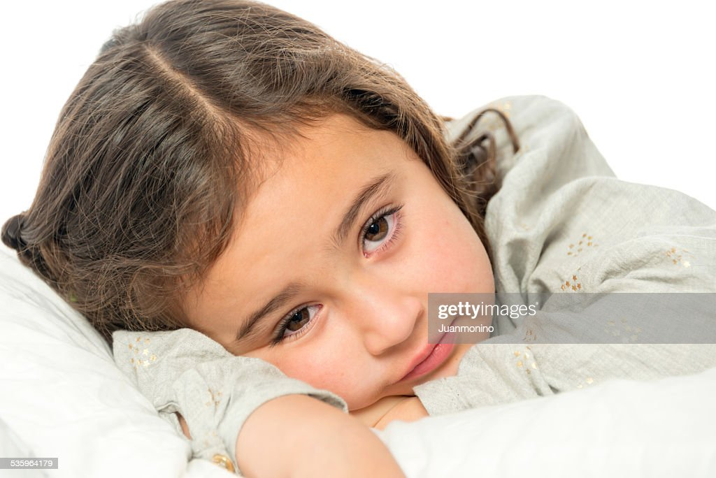 Little girl laying on arms looking at camera with sad face. : Stock Photo