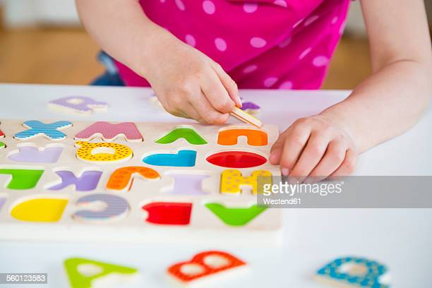 Little girl learning alphabet with wooden letters